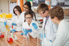 Attentive school kids doing a chemical experiment in laboratory. At school Stock Image