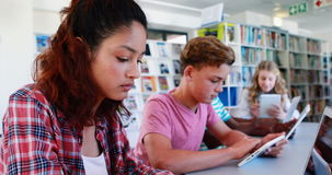 Attentive school kids using laptop and digital tablet in library stock footage
