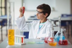 Attentive schoolboy doing a chemical experiment in laboratory. At school Royalty Free Stock Image