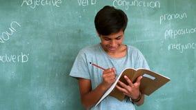 Attentive schoolboy doing homework in classroom stock video