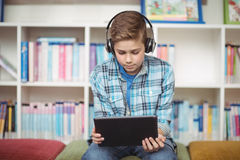 Attentive schoolboy listening music while using digital tablet in library Royalty Free Stock Images