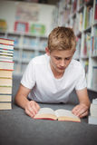 Attentive schoolboy lying on floor and reading book in library Stock Photos