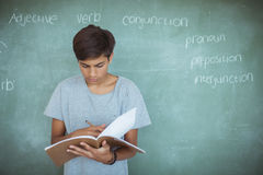 Attentive schoolboy reading book against chalkboard in classroom Royalty Free Stock Photo