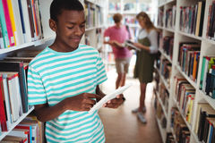 Attentive schoolboy using digital tablet in library Royalty Free Stock Photography