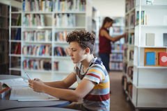 Attentive schoolboy using mobile phone while studying in library. At school Royalty Free Stock Photography