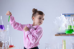 Attentive schoolgirl conducting experiment in lab Stock Photo