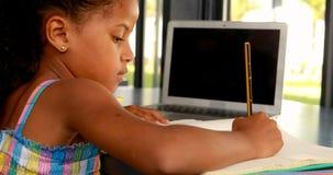Schoolgirl doing homework in library 4k stock footage