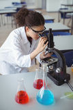 Attentive schoolgirl looking through microscope in laboratory Stock Photos