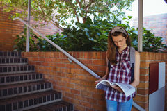 Attentive schoolgirl reading book near staircase Stock Image