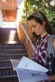 Attentive schoolgirl reading book near staircase Stock Photos