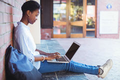 Attentive schoolgirl sitting against brick wall and using laptop Stock Photo