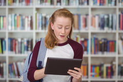 Attentive schoolgirl using digital tablet in library Stock Images