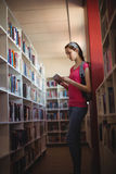 Attentive schoolgirl using digital tablet in library Stock Photos