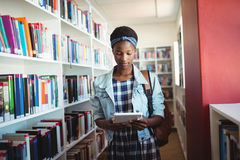 Attentive schoolgirl using digital tablet in library Royalty Free Stock Photos