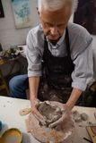 Attentive senior man molding clay Stock Images