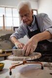Attentive senior man molding clay Royalty Free Stock Photos