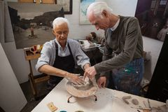 Senior man assisting in making pottery during drawing class Royalty Free Stock Photography