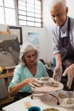 Senior man assisting senior woman in making pottery during drawing class Royalty Free Stock Photography