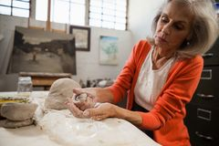 Attentive senior woman molding clay Royalty Free Stock Photography