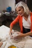 Attentive senior woman molding clay Royalty Free Stock Image
