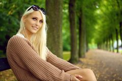 Attentive Sexy Young Blonde Lady. An attentive sexy young blonde woman in a tan jersey sits on a park bench looking upwards with empty tree lined avenue behind Royalty Free Stock Photo