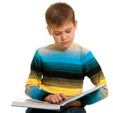 Attentive slim boy reading a thick book Stock Photos
