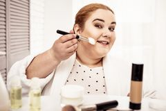 Attentive smiling plus-size woman using cosmetic brush royalty free stock photo