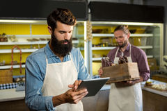 Attentive staff using digital tablet at bakery counter Stock Photos