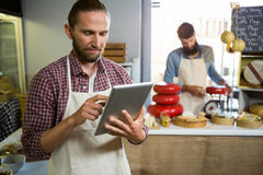 Attentive staff using digital tablet at counter Stock Photos
