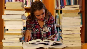 Attentive student studying in the library surrounded by books Royalty Free Stock Images