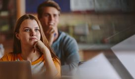Attentive student in university classroom. Pretty teenage student paying attention to lecture in classroom. Woman studying at the college classroom Stock Image