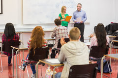 Attentive students with teacher in the classroom Royalty Free Stock Photos