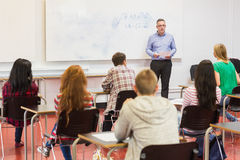 Attentive students with teacher in the classroom. Rear view of students attentively listening to male teacher in the classroom Royalty Free Stock Images