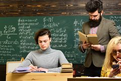 Attentive students writing something in their note pads while sitting at desks in the classroom. Students are royalty free stock photos