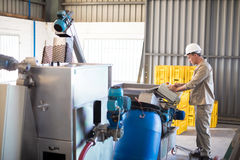 Attentive technician operating a machine. In oil factory Stock Image