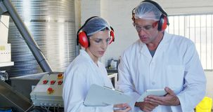 Technicians discussing in oil factory. Attentive technicians discussing in oil factory stock footage