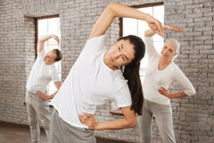 Attentive tutor stooping his back. Look at me. Positive delighted female standing behind her instructor keeping right hand above her head while putting left hand Royalty Free Stock Image