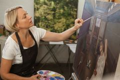Attentive woman painting on canvas. In drawing class stock photo
