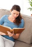 Attentive woman reading a book sitting on her sofa Royalty Free Stock Images