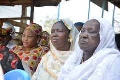 Attentive women. These women sitting under that tarp listen attentively to the teacher of the ceremony . Ivory coast , abidjan on 26february 2015 Stock Photography