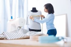 Attentive worker of an atelier measuring a new blouse Royalty Free Stock Image