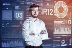 Calm man standing with his arms crossed and looking at the transparent screen. Attentive worker. Serious reliable programmer in a white shirt standing with his royalty free stock images