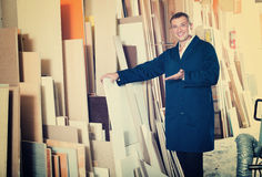 Attentive workman standing with plywood pieces Royalty Free Stock Photography