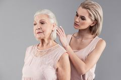 Attentive young blonde girl correcting hairstyle of her old mother royalty free stock photography