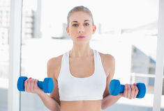 Attentive young blonde model exercising with dumbbells Stock Photo