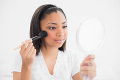 Attentive young dark haired model applying powder on her face Stock Photo