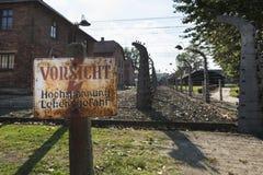 Attento, ad alta tensione, il pericolo firma dentro il campo di Auschwitz II-Birkenau in Brzezinka Immagine Stock