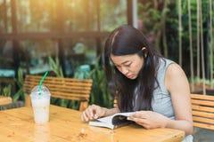 Attenzione asiatica di retribuzione per giorni festivi non lavorativi delle donne nell'istruzione nel giardino del caffè Fotografie Stock