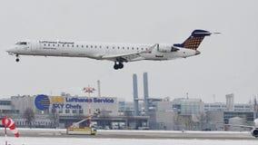 Atterraggio del bombardiere CRJ-900 D-ACNR di Lufthansa CityLine sulla pista nevosa stock footage