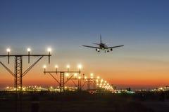 Atterraggio di aeroplano al tramonto fotografia stock